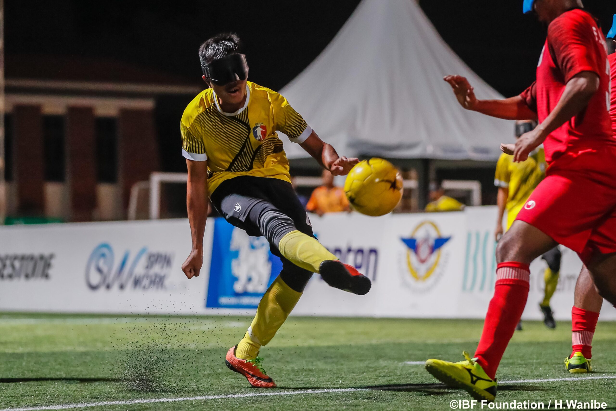 A blind football player strikes the ball into the air